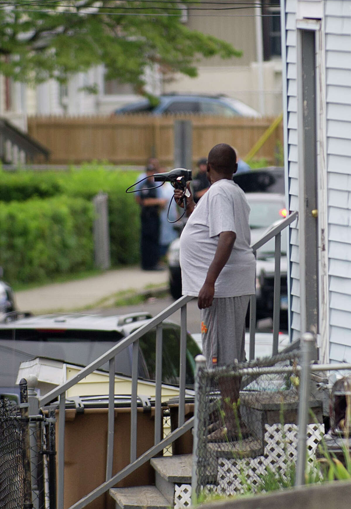A man holding a hair dryer exits the house at 100 Warren Street in Stamford, Conn., where he was subsequently arrested by police who were called for a report of a possibly suicidal man with a gun on Thursday, August 1, 2013.