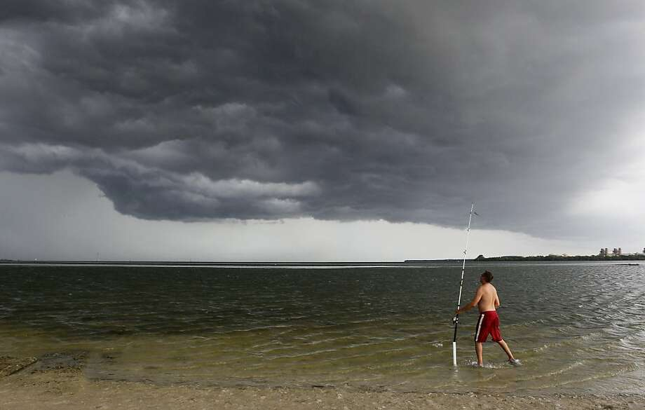 He'll catch lightning if he's not careful:David Lauricella checks his fishing pole as a   storm rolls in over Gandy Beach in St. Petersburg, Fla. Lauricella said he witnessed   several funnel clouds and water spouts while fishing the previous day. Photo: Shadd, Dirk, Associated Press