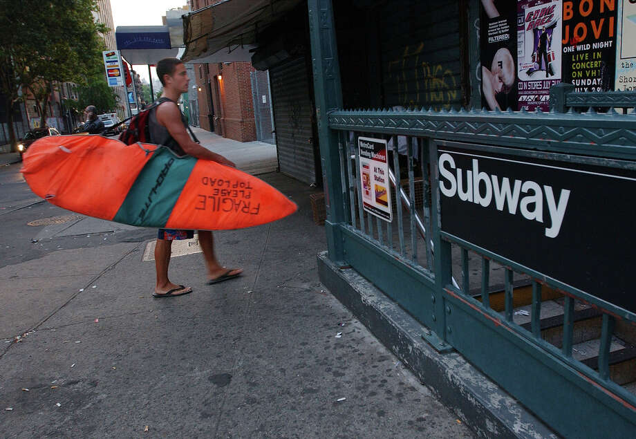 Surfer Paul Treacy carries his surfboard to the New York City Subway August 2, 2001 as he starts his hour-long trek from his Manhattan apartment to Rockaway Beach. Treacy, an Irish native who has traveled the globe in search of perfect waves, is part of a small number of dedicated New York City surfers who ride the subway daily to satisfy their wave-riding addictions. Photo: Spencer Platt, Getty Images / Getty Images North America