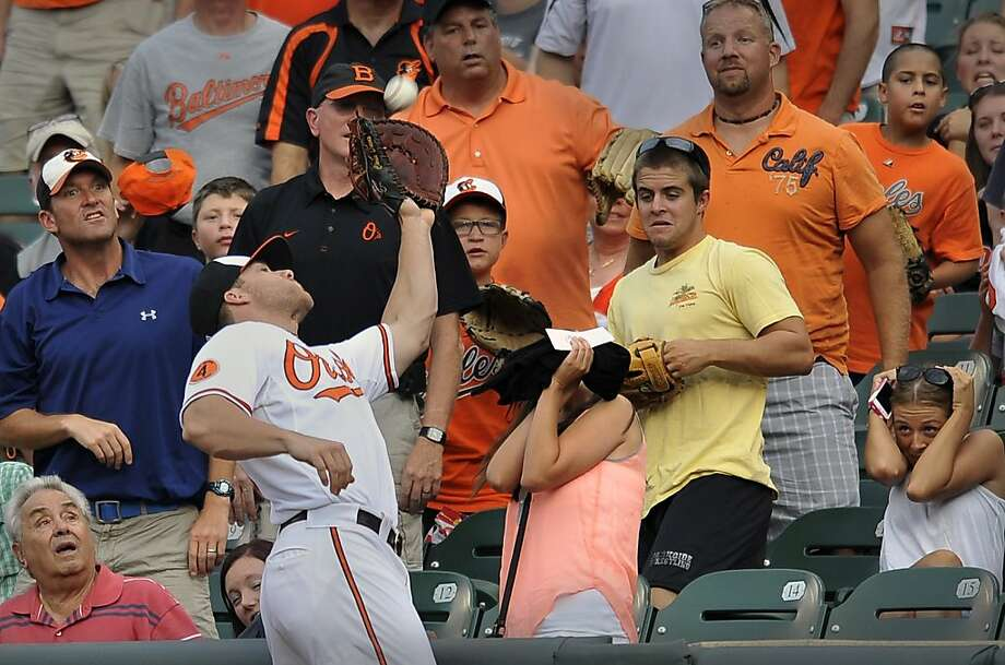 Uh-O's:A fan loses her head as Orioles first baseman Chris Davis reaches into the crowd to snag a foul ball at Camden Yards. Photo: Gail Burton, Associated Press