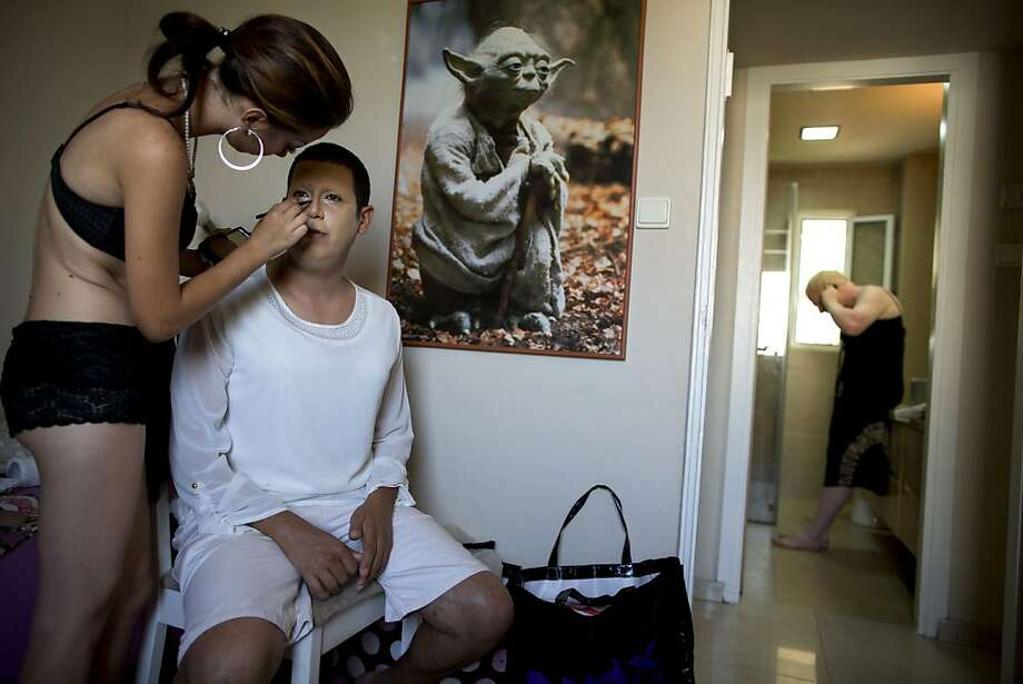 Apply eyeliner, I will: A friend helps Israeli Orthodox Jew Shahar Hadar with his makeup as he prepares for the 