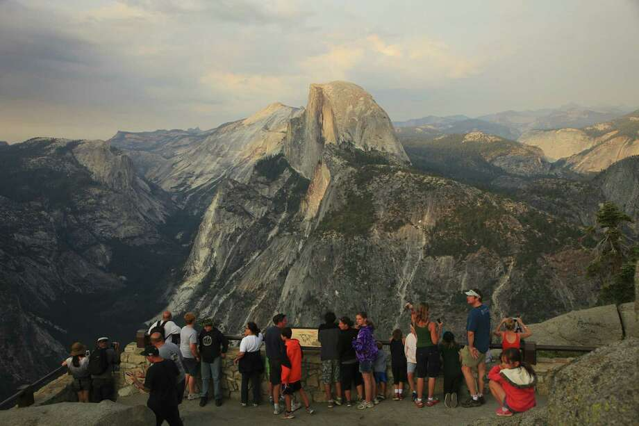Visitors to Glacier Point look out on Half Dome at Yosemite National Park. The National Park Service is considering proposals to handle the crowds at the popular park in California. Photo: Jim Wilson, New York Times