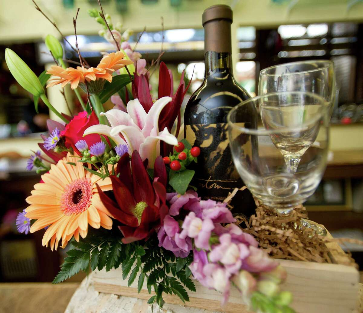 Bouquets and gift arrangements including bottles of wine sit on display at Stamford Florist on Thursday, August 1, 2013.
