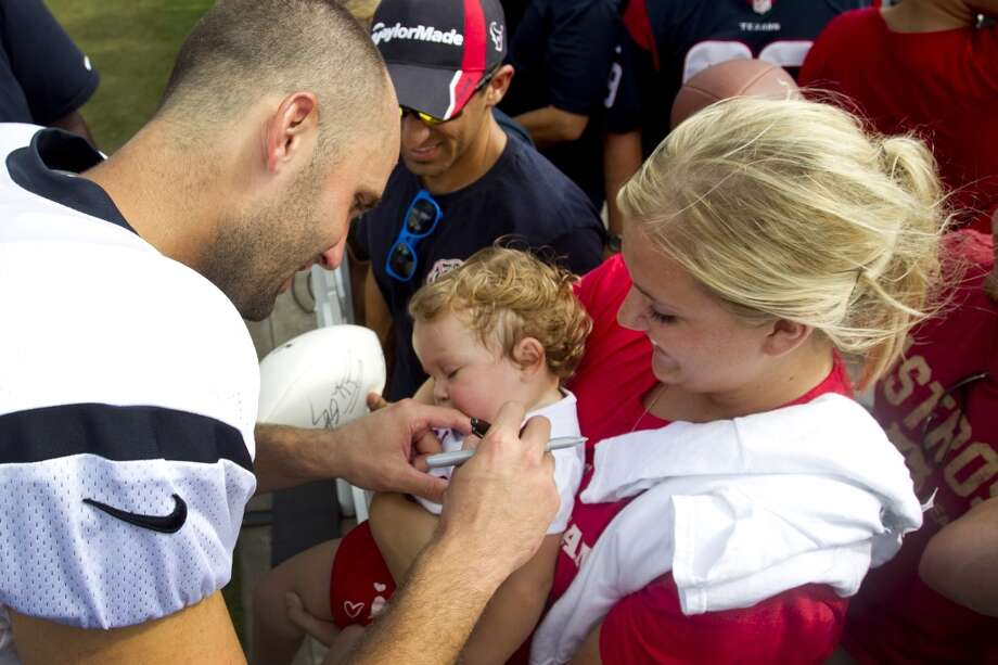 Texans quarterback Matt Schaub autographs the shirt of sleeping Ava Floyd, held by her aunt, Brittany Morgan after practice. Photo: Brett Coomer, Houston Chronicle