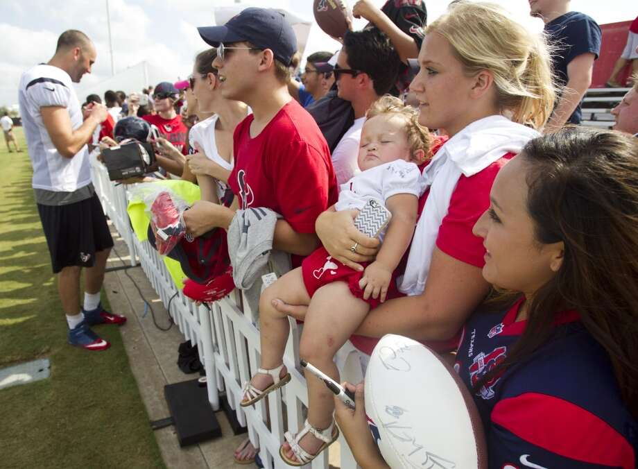 Ava Floyd sleeps in the arms of her aunt, Brittany Morgan as they wait for Texans quarterback Matt Schaub to sign autographs. Photo: Brett Coomer, Houston Chronicle