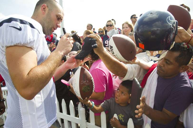 Texans quarterback Matt Schaub signs autographs following practice.