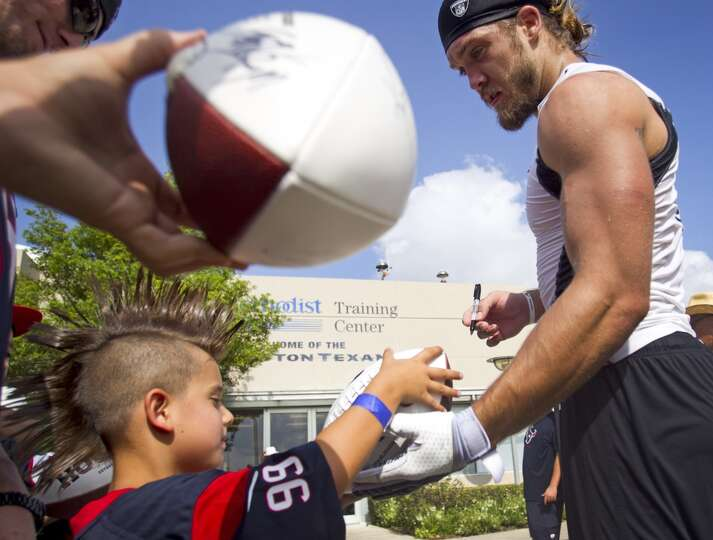 Kross Lowery,6, left, gets an autograph from Texans linebacker Bryan Braman following practice.