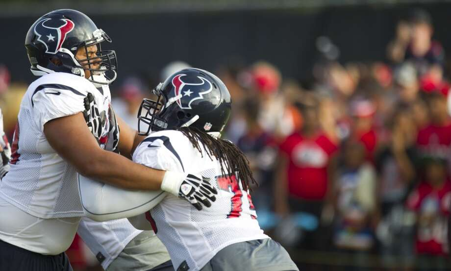 Texans tackles Ryan Harris and Derek Newton work on blocking drills. Photo: Brett Coomer, Houston Chronicle