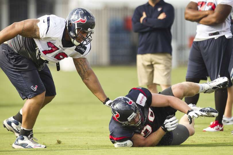 Texans guard Brandon Brooks pushes defensive end J.J. Watt to the ground during a pass rush drill.