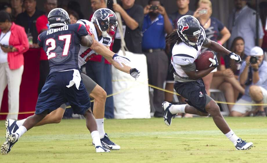 Texans wide receiver Keshawn Martin, right, returns a kick past Travis Howard and Andy Cruse during a special teams drill. Photo: Brett Coomer, Houston Chronicle