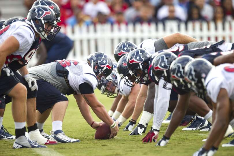 Texans long snapper Jon Weeks lines up over the ball during a special teams drill.