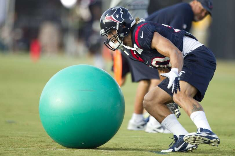 Texans linebacker Bryan Braman runs to grab a ball during a drill.