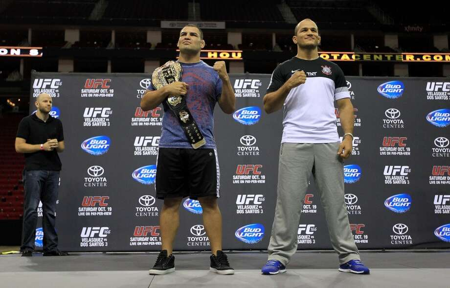 Cain Velasquez, left, stands with Junior dos Santos, right, during an open workout with the UFC heavyweight champion Velasquez and former champion dos Santos at Toyota Center, Thursday, Aug. 1, 2013, in Houston. It was free and open to the public as they talked about their upcoming pay-per-view fight which will take place Saturday, October 19 at Toyota Center.  ( Karen Warren / Houston Chronicle ) Photo: Karen Warren, Houston Chronicle