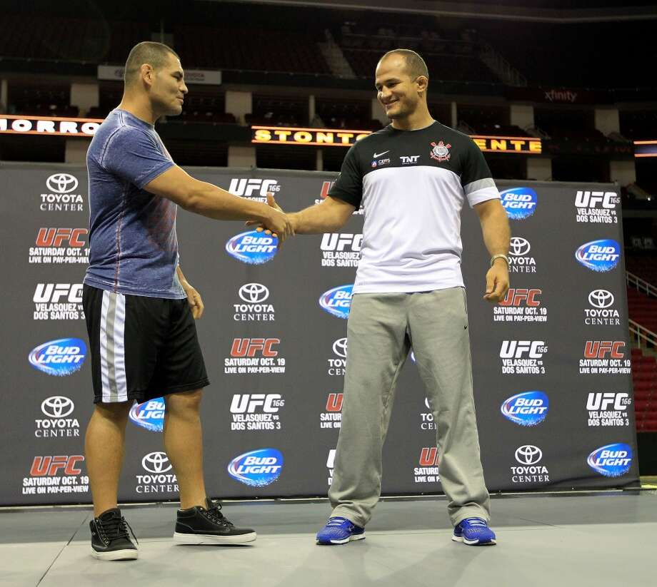 Cain Velasquez, left, shakes hands with Junior dos Santos, right, during an open workout with the UFC heavyweight champion Velasquez and former champion dos Santos at Toyota Center, Thursday, Aug. 1, 2013, in Houston. It was free and open to the public as they talked about their upcoming pay-per-view fight which will take place Saturday, October 19 at Toyota Center.  ( Karen Warren / Houston Chronicle ) Photo: Karen Warren, Houston Chronicle