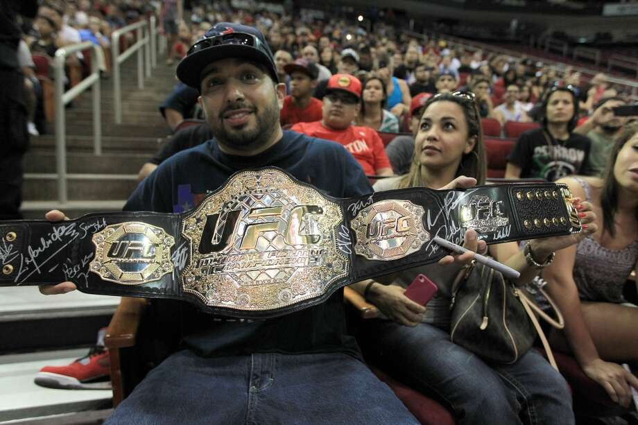 UFC fan David Canales holds up his belt during an open workout with UFC heavyweight champion Cain Velasquez and former champion Junior dos Santos at Toyota Center, Thursday, Aug. 1, 2013, in Houston. It was free and open to the public as they talked about their upcoming pay-per-view fight which will take place Saturday, October 19 at Toyota Center.  ( Karen Warren / Houston Chronicle ) Photo: Karen Warren, Houston Chronicle
