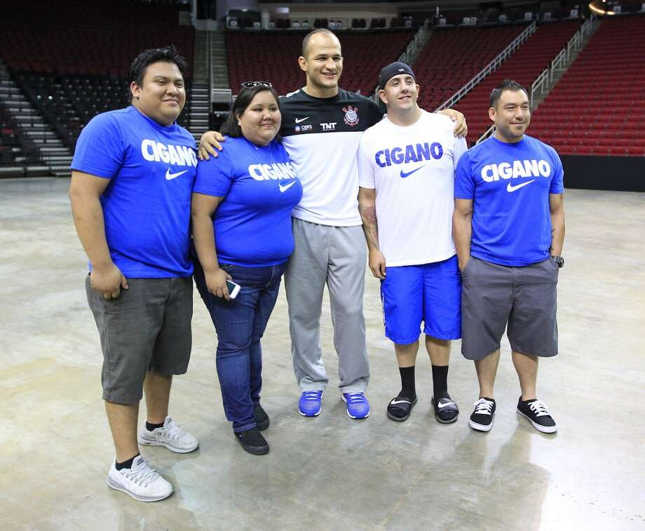 Junior dos Santos gets his photo taken with fans wearing his Nike t-shirts (Estuardo Hernandez, Dianna Mancillas, Tristan Evans, and Michael Lopez) during an open workout with UFC heavyweight champion Cain Velasquez and former champion Junior dos Santos at Toyota Center, Thursday, Aug. 1, 2013, in Houston. It was free and open to the public as they talked about their upcoming pay-per-view fight which will take place Saturday, October 19 at Toyota Center.  ( Karen Warren / Houston Chronicle ) Photo: Karen Warren, Houston Chronicle