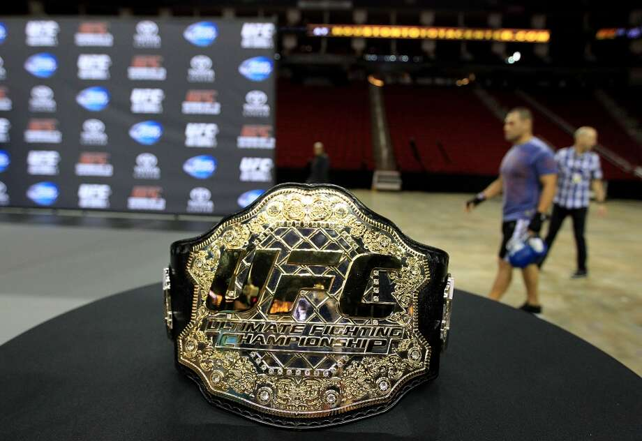 The Heavyweight champion belt sits on a table as Cain Velasquez  walks out to the stage during an open workout with UFC heavyweight champion Cain Velasquez and former champion Junior dos Santos at Toyota Center, Thursday, Aug. 1, 2013, in Houston. It was free and open to the public as they talked about their upcoming pay-per-view fight which will take place Saturday, October 19 at Toyota Center.  ( Karen Warren / Houston Chronicle ) Photo: Karen Warren, Houston Chronicle