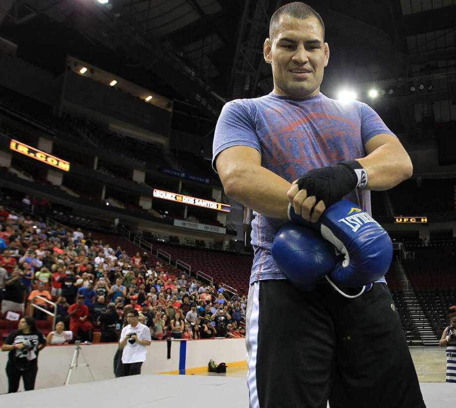 Cain Velasquez takes off his gloves after sparring during an open workout with UFC heavyweight champion Cain Velasquez and former champion Junior dos Santos at Toyota Center, Thursday, Aug. 1, 2013, in Houston. It was free and open to the public as they talked about their upcoming pay-per-view fight which will take place Saturday, October 19 at Toyota Center.  ( Karen Warren / Houston Chronicle ) Photo: Karen Warren, Houston Chronicle