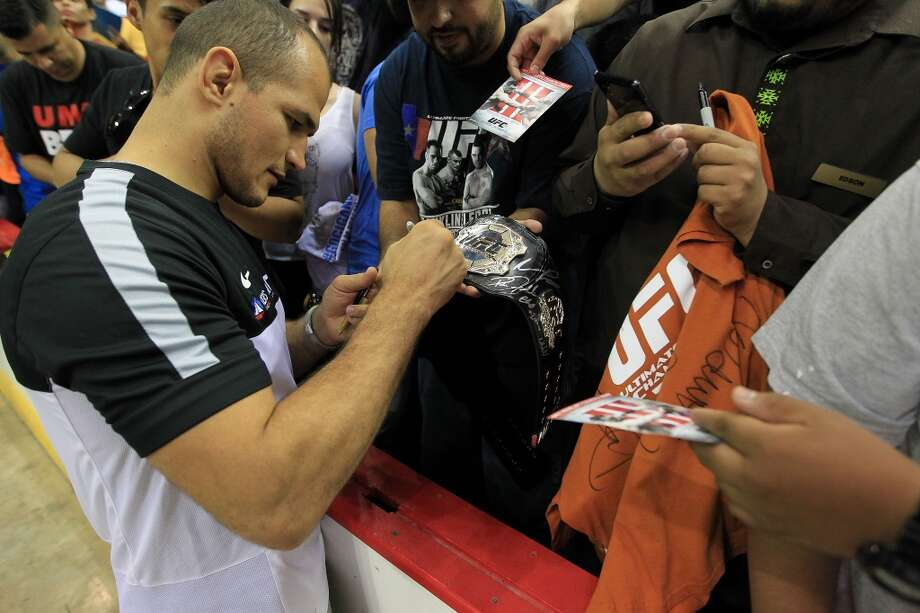 Junior dos Santos signs autographs for fans during an open workout with UFC heavyweight champion Cain Velasquez and former champion Junior dos Santos at Toyota Center, Thursday, Aug. 1, 2013, in Houston. It was free and open to the public as they talked about their upcoming pay-per-view fight which will take place Saturday, October 19 at Toyota Center.  ( Karen Warren / Houston Chronicle ) Photo: Karen Warren, Houston Chronicle