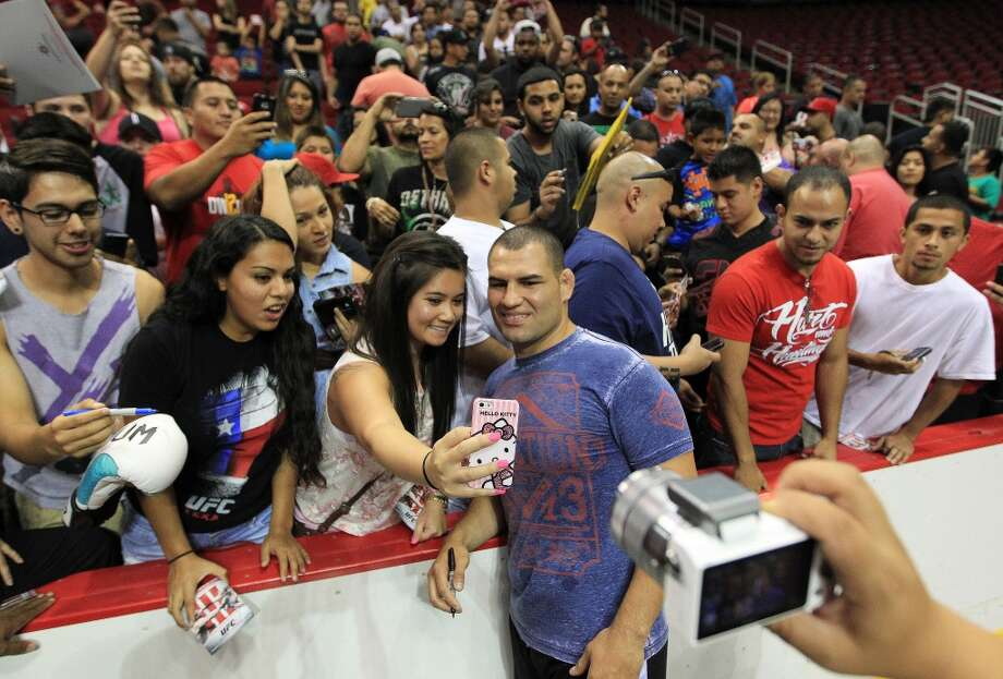 Cain Velasquez takes a photo with Nhi Nguyen as he signed autographs during an open workout with UFC heavyweight champion Cain Velasquez and former champion Junior dos Santos at Toyota Center, Thursday, Aug. 1, 2013, in Houston. It was free and open to the public as they talked about their upcoming pay-per-view fight which will take place Saturday, October 19 at Toyota Center.  ( Karen Warren / Houston Chronicle ) Photo: Karen Warren, Houston Chronicle