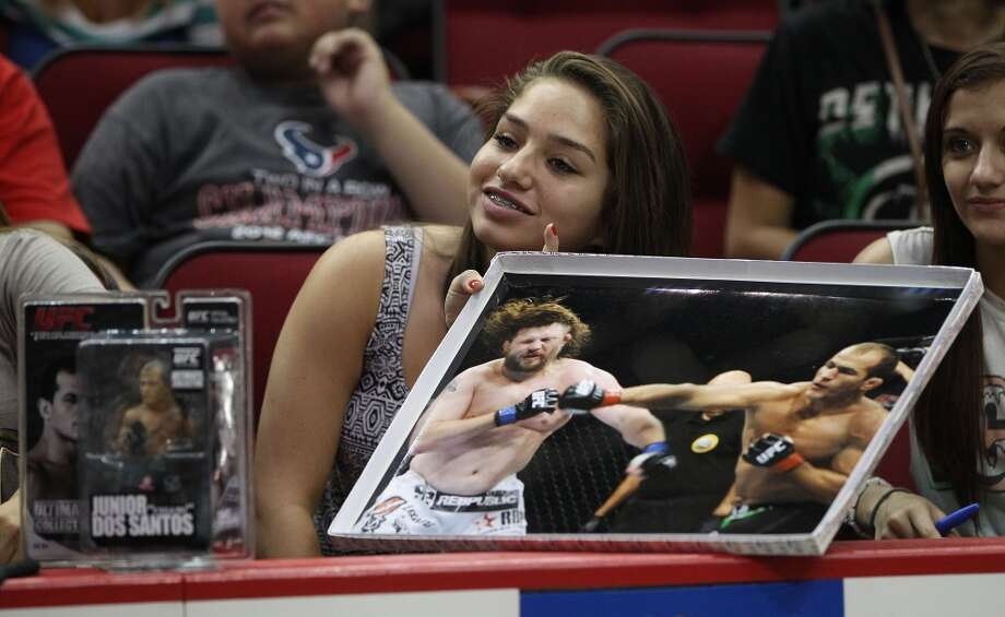 Aliyah Canales, 14, holds a photo of Junior dos Santos fighting against Roy Nelson as she listens to dos Santos speak during an open workout with UFC heavyweight champion Cain Velasquez and former champion Junior dos Santos at Toyota Center, Thursday, Aug. 1, 2013, in Houston. It was free and open to the public as they talked about their upcoming pay-per-view fight which will take place Saturday, October 19 at Toyota Center.  ( Karen Warren / Houston Chronicle ) Photo: Karen Warren, Houston Chronicle