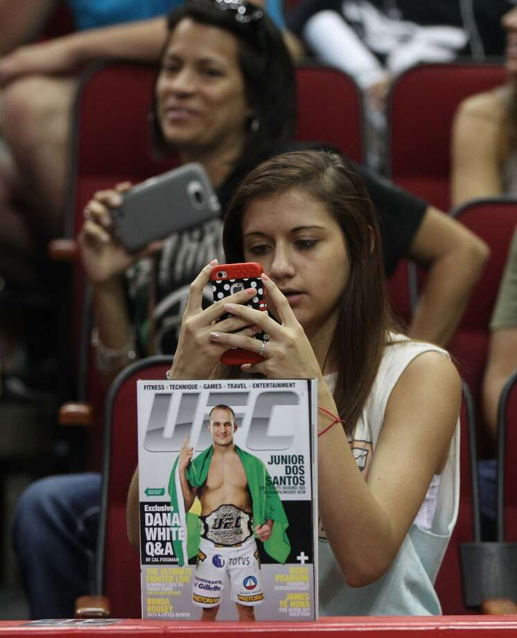 Hailey Lopez, 15, takes a photo of Junior dos Santos during an open workout with UFC heavyweight champion Cain Velasquez and former champion Junior dos Santos at Toyota Center, Thursday, Aug. 1, 2013, in Houston. It was free and open to the public as they talked about their upcoming pay-per-view fight which will take place Saturday, October 19 at Toyota Center.  ( Karen Warren / Houston Chronicle ) Photo: Karen Warren, Houston Chronicle