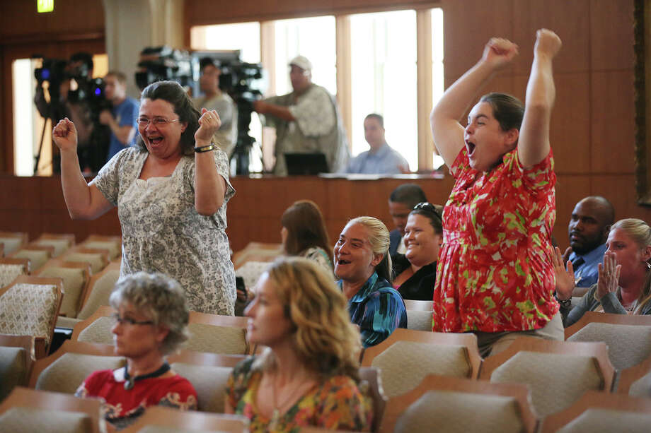 Stephanie McMeans, standing left, and Emily Benson, standing right, celebrate after the San Antonio City Council votes to approve new regulations for the horse carriage industry, Thursday, August 1, 2013. In back are animal rights activist that wanted the city to ban the practice. Photo: JERRY LARA, San Antonio Express-News / © 2013 San Antonio Express-News