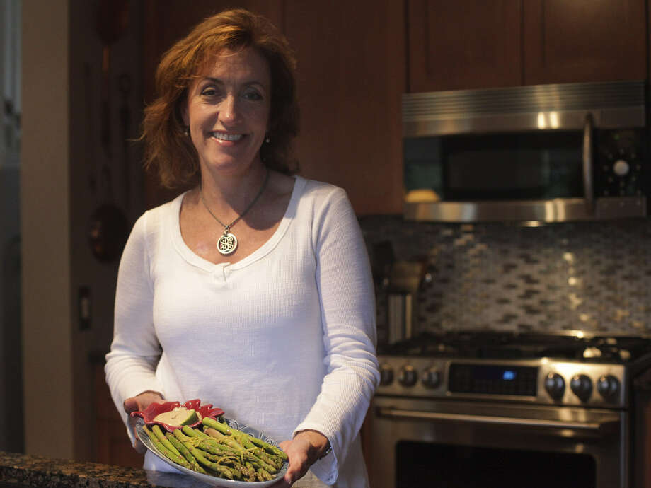 Elizabeth Hallier, who was trained at Le Cordon Bleu, prepares asparagus with avocado mayonnaise. Though she always loved to cook, Hallier pursued a business career first. Photo: Abbey Oldham / San Antonio Express-News