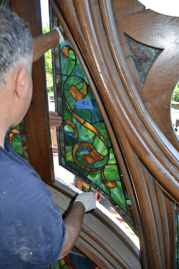 With a helping hand on the other side, a craftsman from the J&R Lamb Studios removes a piece of stained glass from the frame of a large window at Southport Congregational Church. The roughly 300-square-foot, 106-year-old stained glass window is badly deteriorated and has been shipped in sections to Lamb's New Jersey studio to be restored. July 31, 2013. Fairfield CT. Photo: Contributed Photo / Fairfield Citizen