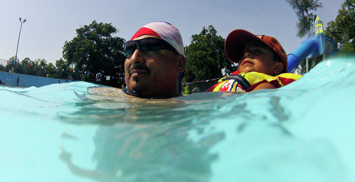 Ronney Martinez (left) and his son Richard Martinez, 2, cool off at Roosevelt Pool Thursday Aug. 1, 2013.