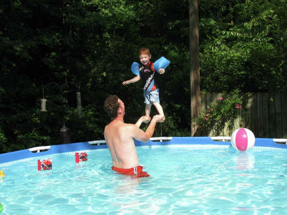 "Two-year-old Jack Lockart Jr. stands on his dad John's hands as they keep cool in their Colonie pool during the recent heat wave. ""They are doing what they call their 'balancing act' ... Jack loves standing way up high on daddy's hands and then he jumps right in,"" says mom Tara Lockart."