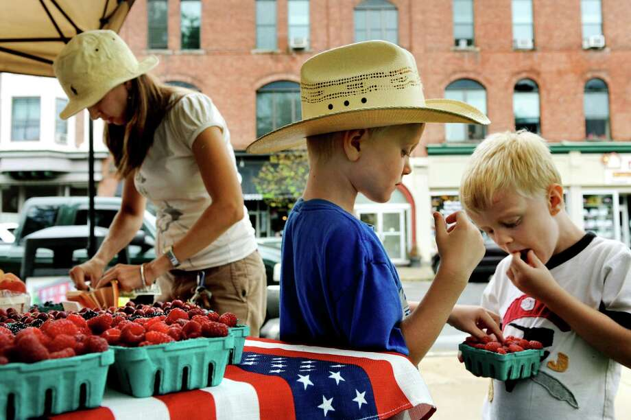 Levi Jenkins, 5, of Ballston Spa, center, eats raspberries with his brother Wesley, 4, right, as their mother, Amy, pays for the fruit during the Ballston Spa Farmers Market on Thursday, Aug. 1, 2013, at Wiswall Park in Ballston Spa, N.Y. Vendors sell their wares on Thursdays from 3 to 6 p.m. and Saturdays from  9 a.m. to noon through September 28th. (Cindy Schultz / Times Union) Photo: Cindy Schultz / 00022579A
