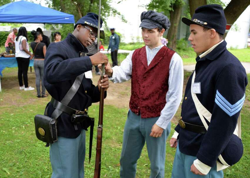 Members of the young abolitionists teen scholar's institute, from left, Nijair Smalls, 15, dressed as a Union 26th U.S. Colored trooper, Sam Levitt, 18, in period dress as an abolitionist veteran, and Wayne Cooperider, 15, is dressed as a Union 26th U.S. Colored troop Sgt. Thursday Aug. 1, 2013, during the Underground Railroad summer project at the Stephen and Harriet Myers Residence in Albany, N.Y. (John Carl D'Annibale / Times Union)