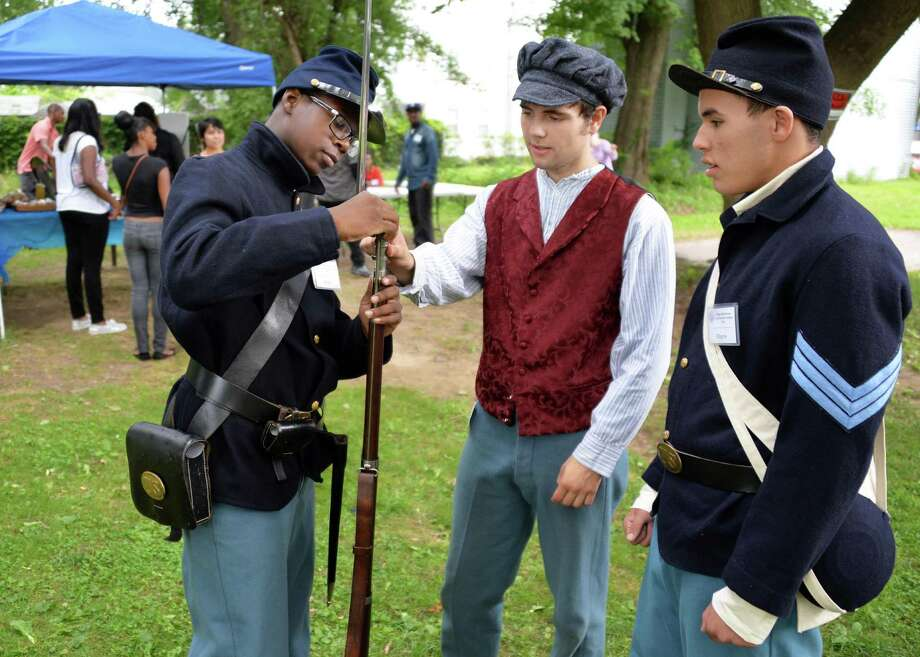Members of the young abolitionists teen scholar's institute, from left, Nijair Smalls, 15, dressed as a Union 26th U.S. Colored trooper,  Sam Levitt, 18, in period dress as an abolitionist veteran, and Wayne Cooperider, 15, is dressed as a Union 26th U.S. Colored troop Sgt. Thursday Aug. 1, 2013, during the Underground Railroad summer project at the Stephen and Harriet Myers Residence in Albany, N.Y. (John Carl D'Annibale / Times Union) Photo: John Carl D'Annibale / 10023366A