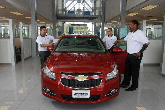 Carlos Chen, left, Andrew Willard and Marckel Thomas look over a 2013 Chevrolet Cruze LTZ at Monument Chevrolet in Pasadena, where the men work.