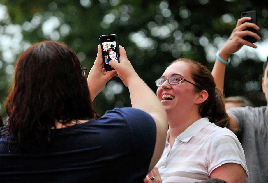 Marissa Fraser, right, watches as her friend Sarah Bojnec, back turned, photographs herself in the front row as Matt Nathanson performs on stage behind her during the Alive@Five concert series at Columbus Park in Stamford on Thursday, Aug. 1, 2013. The Advocate newspaper is a sponsor of the event. Photo: Jason Rearick / Stamford Advocate