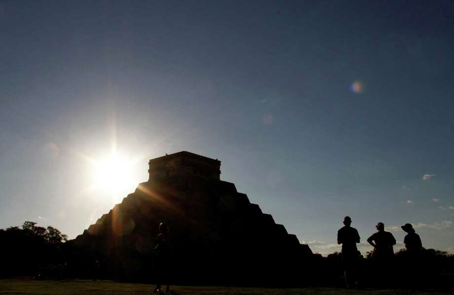 FILE - The sun sets behind the Kukulkan Pyramid in the ancient Mayan city of Chichen Itza in Mexico on Thursday, Dec. 20, 2012. A study published online Thursday, Aug. 1, 2013 by the journal Science says as the world gets warmer, people are more prone to get hot under the collar. Scientists found that aggressive acts like violent crimes and wars become more likely with each added degree. Solomon Hsiang, author of the study, pointed to the collapse of the Mayan civilization that coincided with periods of historic drought about 1200 years ago. (AP Photo/Israel Leal) ORG XMIT: NY116 Photo: Israel Leal / AP