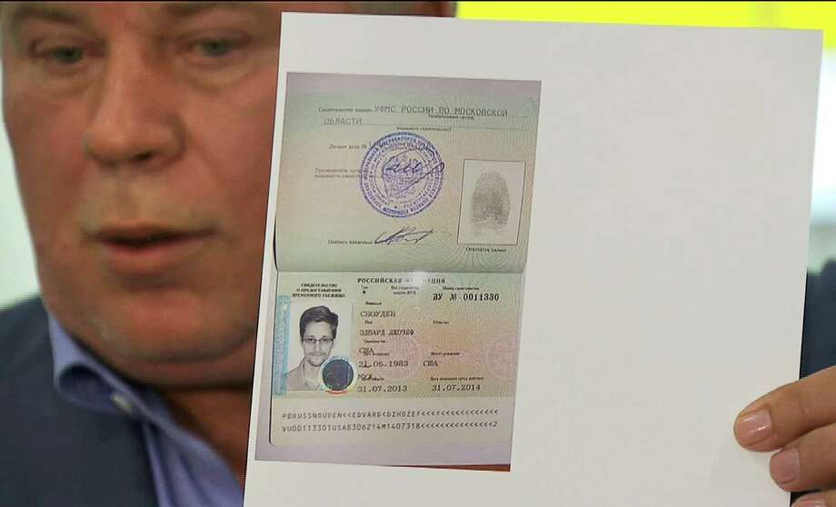 In this image taken from Associated Press Television, Russian lawyer Anatoly Kucherena holds a temporary document that allows Edward Snowden to cross the border into Russia at Sheremetyevo airport outside Moscow on Thursday, Aug. 1, 2013. Snowden, who leaked secrets from the National Security Agency, has received asylum in Russia for one year and left the transit zone of Moscow's airport, his lawyer said Thursday. Kucherena said after meeting with the fugitive at Moscow's Sheremetyevo airport, where he was stuck since his arrival from Hong Kong on June 23, that he handed him the papers proving his status. Kucherena said that Snowden's whereabouts will be kept secret for security reasons. (AP Photo/APTN) ORG XMIT: XAZ107 Photo: Uncredited / Assocoated Press Television