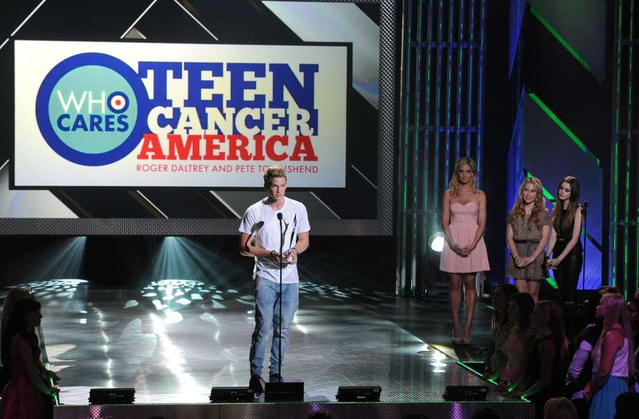 (L-R) Singer Cody Simpson receives the Teen Cancer America Role Model Award as actresses Tara Lipinski (2nd from R) and Laura Marano stand nearby onstage during CW Network's 2013 Young Hollywood Awards presented by Crest 3D White and SodaStream held at The Broad Stage on August 1, 2013 in Santa Monica, California.  (Photo by Kevin Winter/Getty Images for PMC) Photo: Kevin Winter