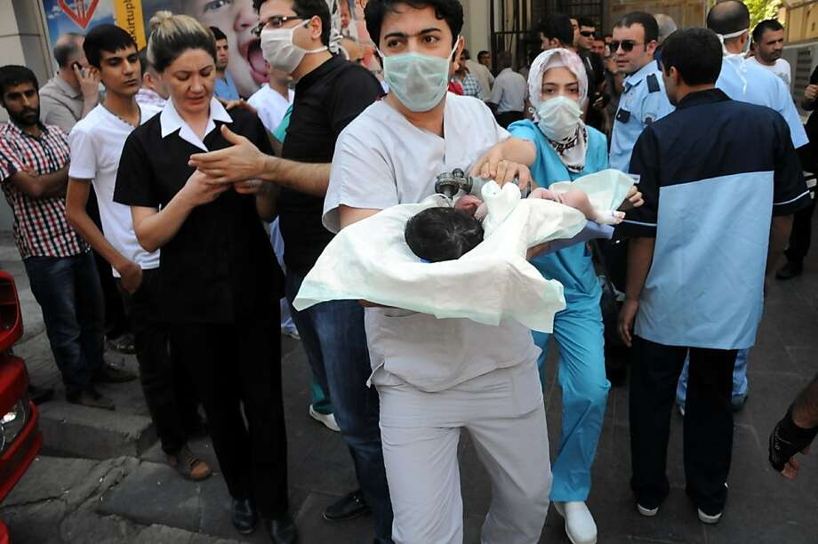 Doctors evacuate a baby from a hospital while a fire is breaking out on August 1, 2013 in the center of Diyarbakir.  AFP PHOTO / MEHMET ENGINMEHMET ENGIN/AFP/Getty Images Photo: Mehmet Engin, AFP/Getty Images