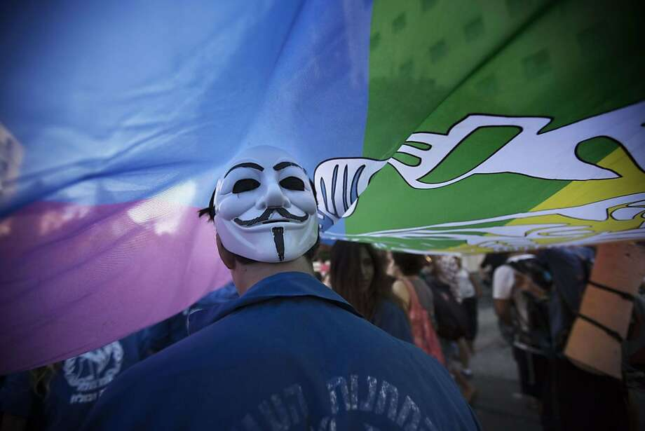 "An Israeli wears a mask of the Anonymous movement under a giant flag during the annual gay pride parade on August 1, 2013 in Jerusalem. 2,500 people took part in the gay pride parade calling for equal rights, as 150 Ultra Orthodox Jews demonstrated to denounce the ""abomination"" of homosexuality.    AFP PHOTO/MENAHEM KAHANAMENAHEM KAHANA/AFP/Getty Images Photo: Menahem Kahana, AFP/Getty Images"