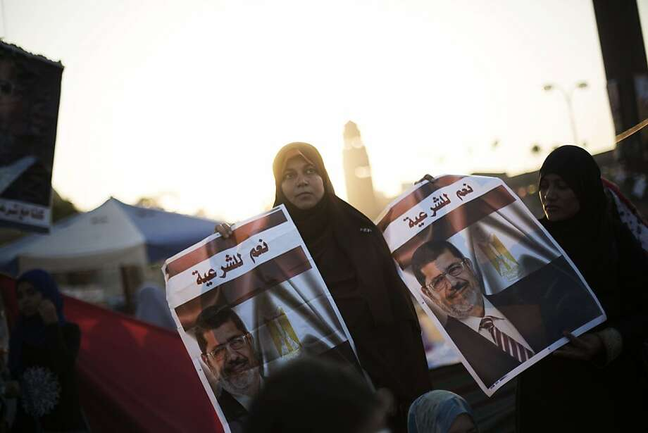 """A woman supporter of Egypt's ousted President Mohammed Morsi holds a banner of the former president  with Arabic that reads """"yes to legitimacy,"""" during a protest near Cairo University in Giza, Egypt, Thursday, August, 1, 2013. Authorities offered """"safe passage and protection"""" Thursday for thousands of supporters of ousted President Mohammed Morsi if they end their two large sit-ins in Cairo. The Interior Ministry's offer appears to be the first step by Egypt's new leadership to clear away the Morsi supporters from where they have been camped since shortly before he was toppled by the army July 3. (AP Photo/Manu Brabo) Photo: Manu Brabo, Associated Press"""