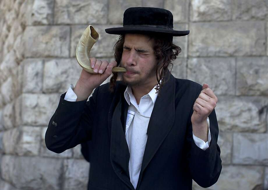 """Tooting intolerance:An Ultra Orthodox Jew blows the Shofar, an instrument made of a ram's   horn, to protest the gay pride parade in Jerusalem. About 150 Ultra Orthodox Jews   rallied to denounce the """"abomination"""" of homosexuality, as some 2,500 people calling for   equal rights marched in the parade. Photo: Ahmad Gharabli, AFP/Getty Images"""