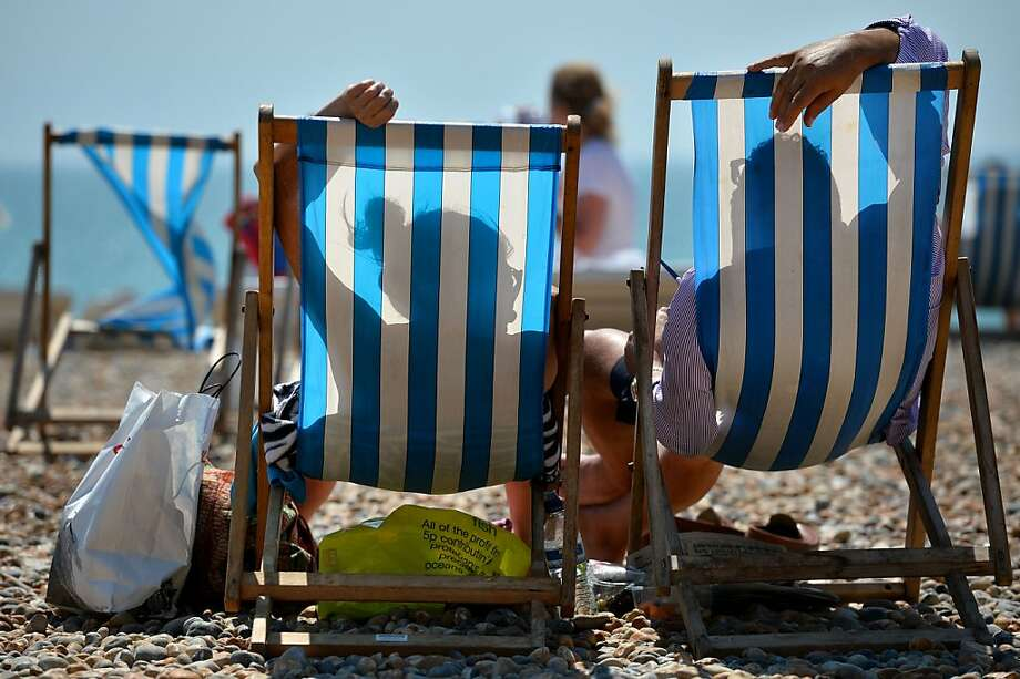 People relaxe in deckchairs on the beach in Brighton, on the south coast during hot weather on August 1, 2013. Temperatures in the south of England were set to rise to over 30C (86F) again as the heatwave briefly returns to the UK. AFP PHOTO / BEN STANSALLBEN STANSALL/AFP/Getty Images Photo: Ben Stansall, AFP/Getty Images