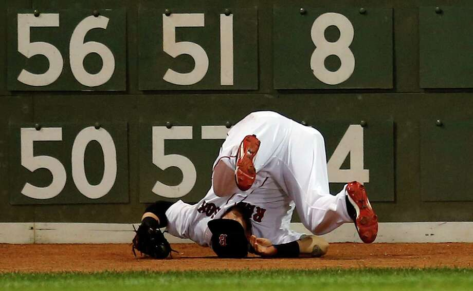 BOSTON, MA - AUGUST 1: Jonny Gomes #5 of the Boston Red Sox rolls over after making a catch on a ball hit by Endy Chavez #9 of the Seattle Mariners in the 9th inning at Fenway Park on August 1, 2013 in Boston, Massachusetts. (Photo by Jim Rogash/Getty Images) ORG XMIT: 163494806 Photo: Jim Rogash / 2013 Getty Images