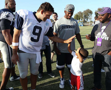 Quarterback Tony Romo (09) offers a high five to Los Angeles Clippers guard Chris Paul's son, Christopher, after the afternoon session of the 2013 Dallas Cowboys training camp on Thursday, Aug. 1, 2013 in Oxnard. Photo: Kin Man Hui, San Antonio Express-News / ©2013 San Antonio Express-News