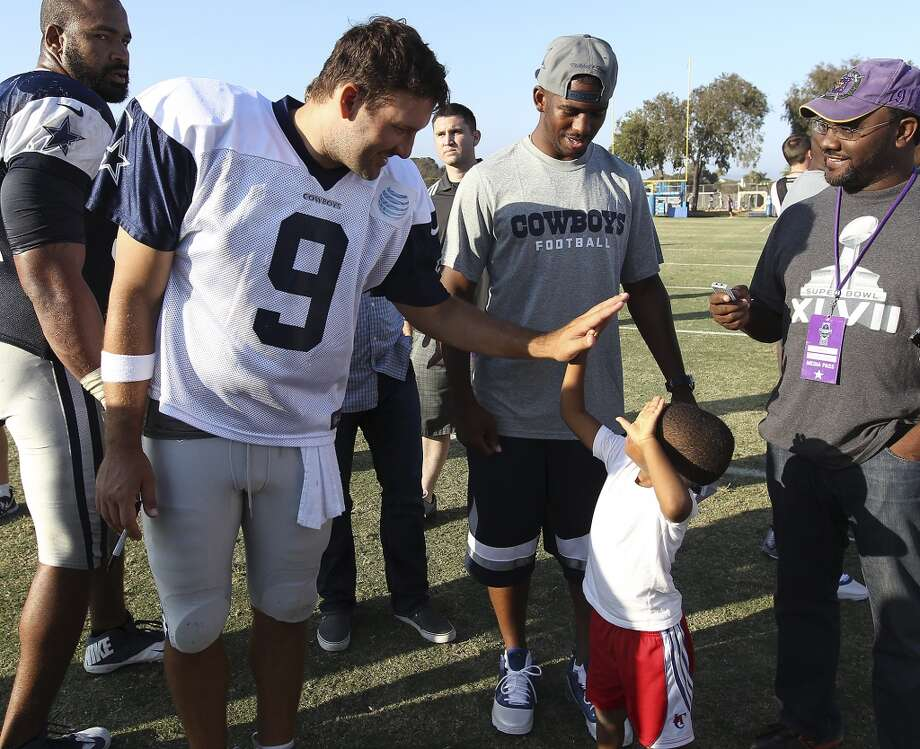 Quarterback Tony Romo (09) offers a high five to Los Angeles Clippers guard Chris Paul's son, Christopher, after the afternoon session of the 2013 Dallas Cowboys training camp on Thursday, Aug. 1, 2013, in Oxnard, Calif. (Kin Man Hui / San Antonio Express-News) Photo: Kin Man Hui, San Antonio Express-News