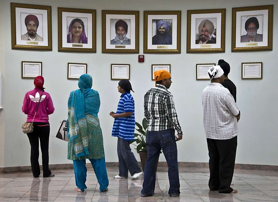Visitors look at a memorial near the entrance of the Sikh Temple of Wisconsin Wednesday, July 31, 2013, in Oak Creek, Wis. Twelve months ago a white supremacist shot and killed six temple members, and the survivors plan to mark the one-year anniversary with solemn religious rites and a candlelight vigil. (AP Photo/Morry Gash) Photo: Morry Gash, Associated Press
