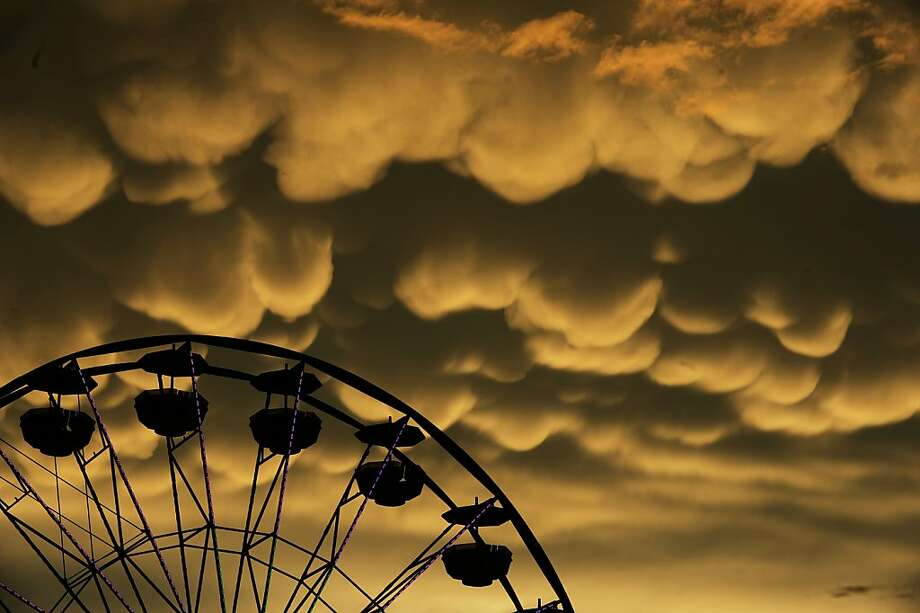 Mammatus clouds move over the Fredericksburg Agricultural Fair after a round of thunderstorms passed through the area on Thursday, Aug. 1, 2013. Mammatus are most often associated with severe thunderstorms.  (AP Photo/The Free Lance-Star, Peter Cihelka) Photo: Peter Cihelka, Associated Press