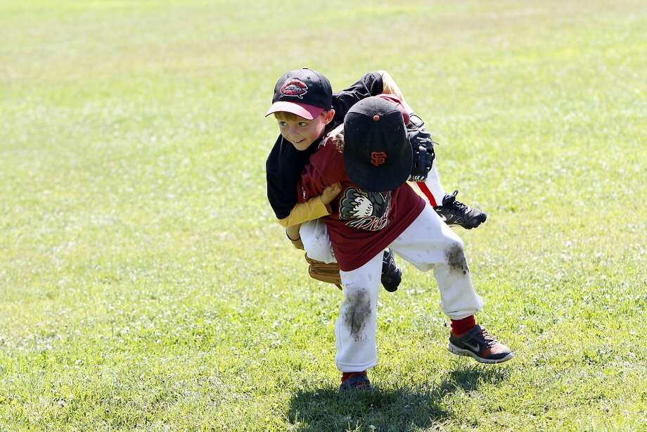 Kaelin Christman, 6, of Mill Valley, gets a piggyback ride off the field from friend Gilbert Roth, 6, of Fairfax, during their baseball camp at Memorial Park in San Anselmo, Calif., Wednesday, July 31, 2013.  The park is slated to be transformed into a habitat that will reduce the impact of floods, but some town residents are furious at the proposed loss of the park. Photo: Special To The Chronicle